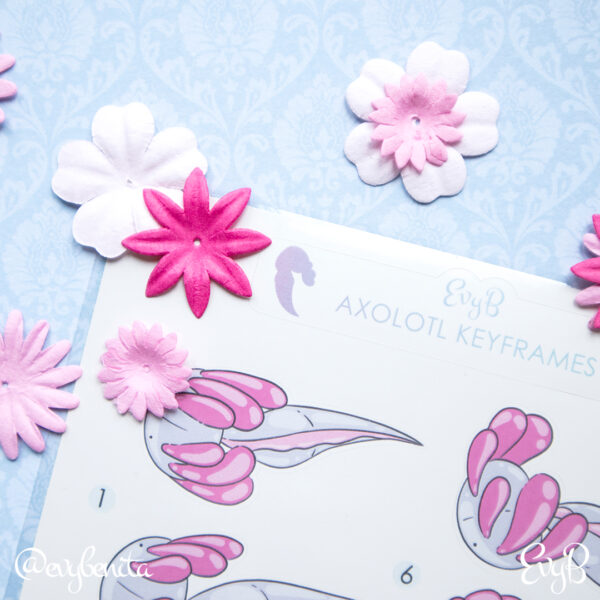 A sheet of axolotl planner stickers by EvyB, surrounded by paper flowers on a blue background.