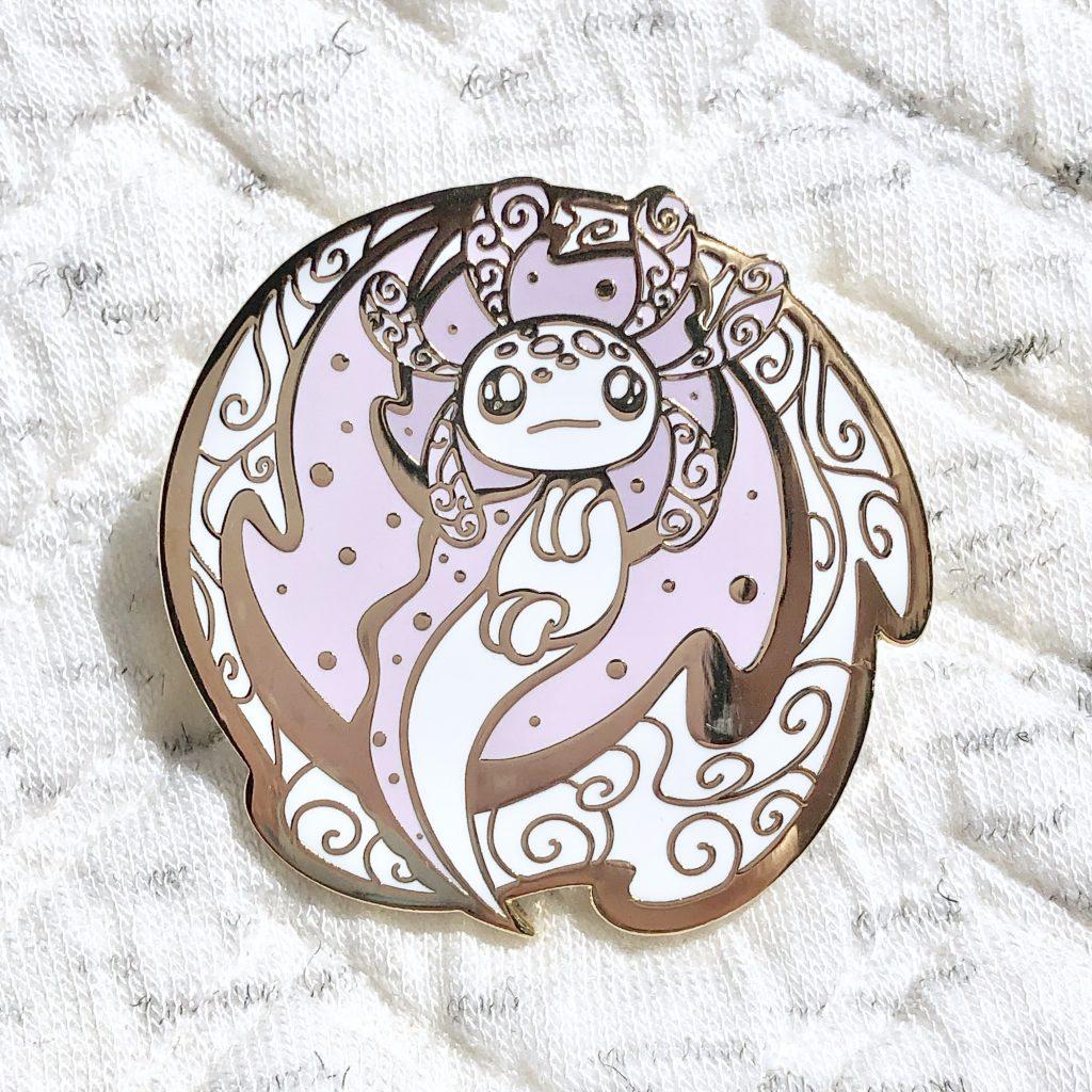Circular, space inspired axolotl enamel pin made from hard enamel and gold plating.