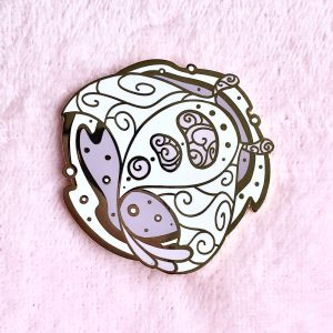 An enamel pin depicting a Manta Ray seen from above, backed by a nebulae. The pin is backed by a pink fabric background.