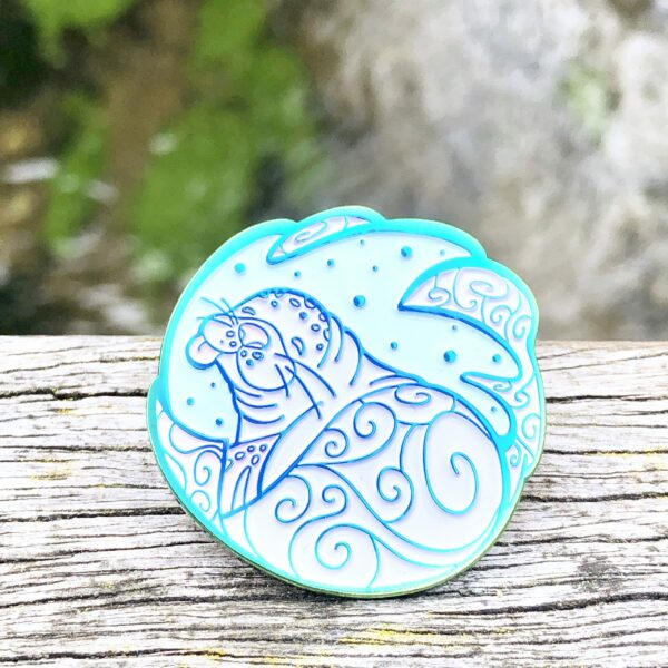 A Hawaiian Monk Seal enamel pin with its tongue out, resting on the fence of a bridge, looking happy.