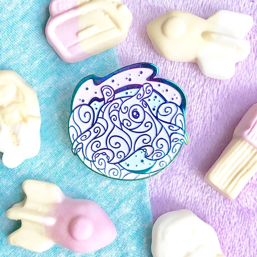 A dumbo octopus enamel pin in rainbow metal, surrounded by foam candies shaped like space ships and other fun shapes.