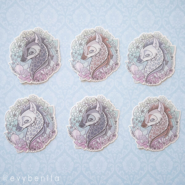 A 2 by 3 grid of stickers, two of each variation. Each sticker shows a hyena's head in the center, surrounded by vines, leaves and flowers, in a light nature palette.