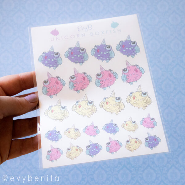 A sticker sheet of unicorn boxfish stickers in a cute cartoony aesthetic. The sticker sheet is held up against the camera on a blue background. The stickers on the sheet come in three colors (purple, pink and yellow), and in two size varieties.