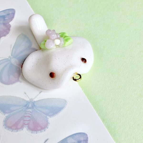 White glitter polymer clay charm of a ghost stingray decorated with flowers and leaves.