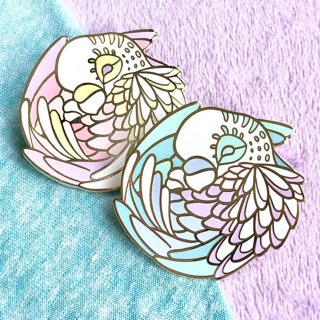 Both color variations of the sleepy parakeet enamel pins.