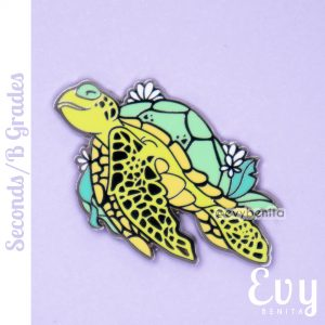 A green sea turtle hard enamel pin with outlines in raised gold metal.