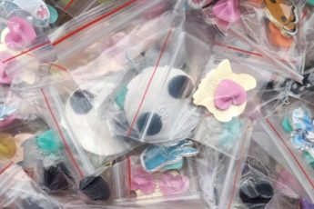 A pile of enamel pins packed in plastic bags and ready to be shipped.