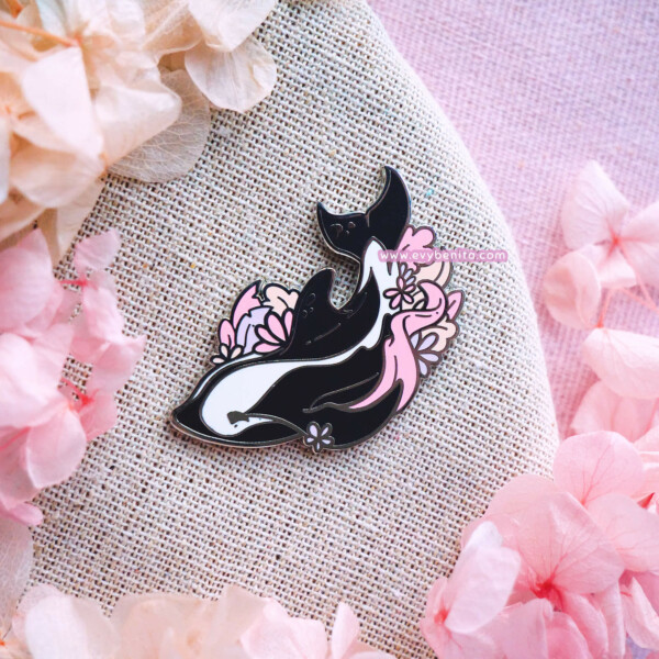A cute hard enamel pin featuring an hourglass dolphin surrounded by pink and peach seaweed.