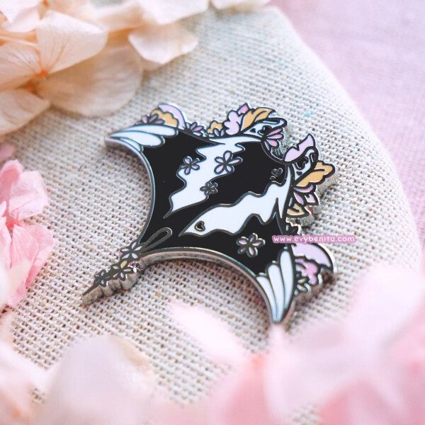 An enamel pin badge with silver-plated raised metal outlines, featuring a giant oceanic manta ray from bird's eye view, decorated by leaves and flowers.