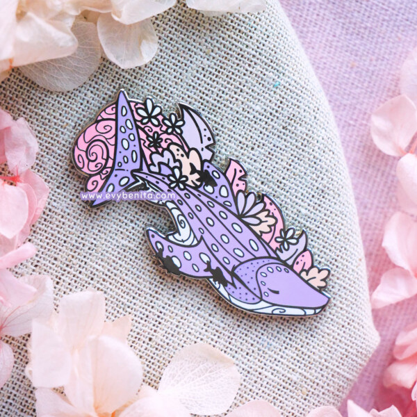 A lapel pin featuring a purple whale shark in a semi-realistic art style. The whale shark is surrounded by pink, beige and purple seaweed and the silhouettes of smaller sucker fish. The whale shark has a tranquil pose and facial expression. The pin is presented on a light blue backing card, designed to represent the sea.