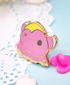 A cute cartoon-style dumbo octopus enamel pin with one eye closed, weighed down by a yellow starfish slumped over the left side of his head. This octopus pin badge has raised outlines in gold plated metal. Shown in perspective next to its pink rubber heart clutch.
