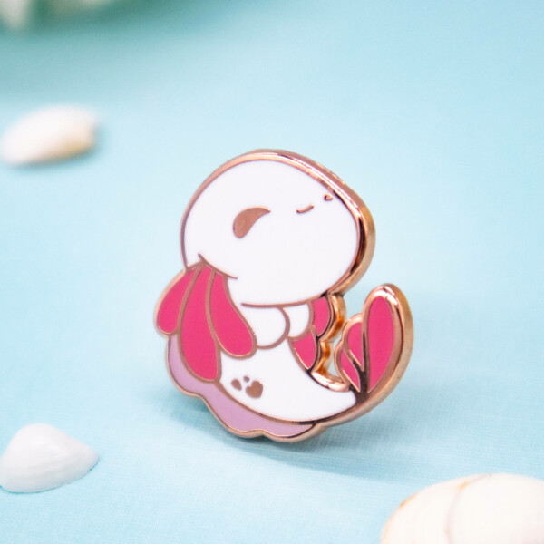A cute cartoon style axolotl hard enamel pin with raised edges in rose gold plated metal
