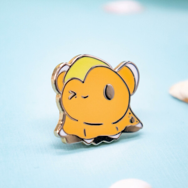 A cute cartoon-style flapjack octopus enamel pin with one eye closed, weighed down by a yellow starfish slumped over the left side of his head. This octopus pin badge has raised outlines in gold plated metal.
