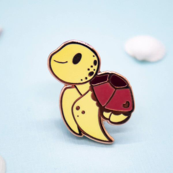 A cute cartoon-style sea turtle enamel pin with exaggerated baby features: big eyes, large front fins and a small shell. The sea turtle pin has raised metal edges outlining the design, which are plated with a rose gold effect.