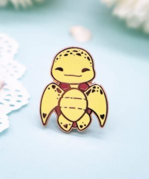 "A hard enamel pin featuring a ""chibi"" cartoon style baby sea turtle. The sea turtle is facing the viewer with both face and body, in a ""humanoid upright"" position. The pin badge has raised metal edges outlining the design, plated with a rose gold effect."