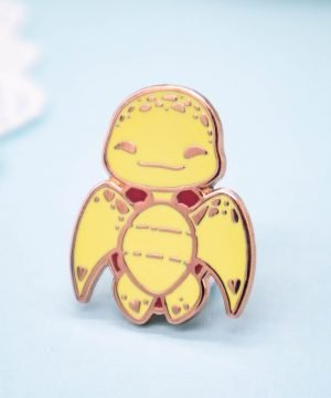 "A hard enamel pin seen in perspective, featuring a ""chibi"" cartoon style baby sea turtle. The sea turtle is facing the viewer with both face and body, in a ""humanoid upright"" position. The pin badge has raised metal edges outlining the design, plated with a rose gold effect."