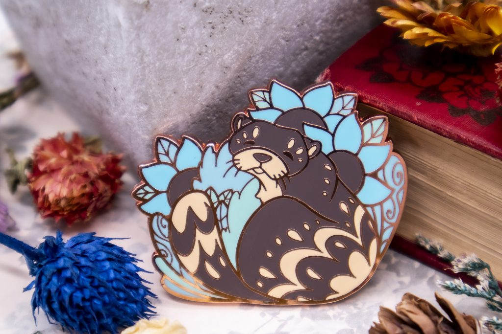 A rose god-plated enamel pin featuring a river otter.
