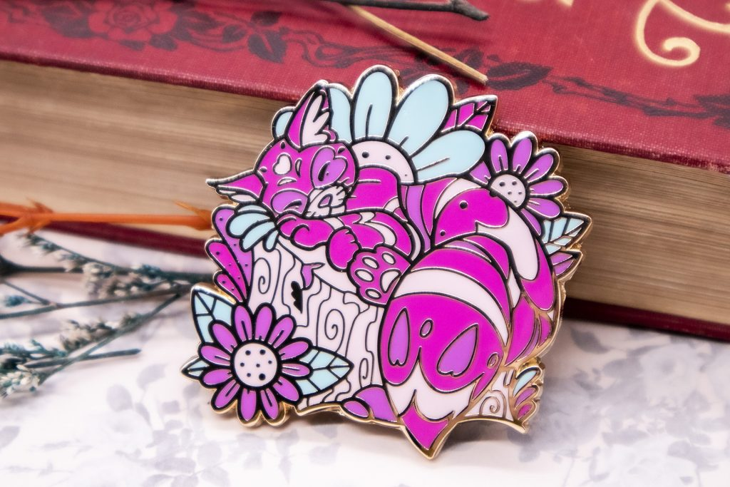 A hard enamel pin featuring a Cheshire cat