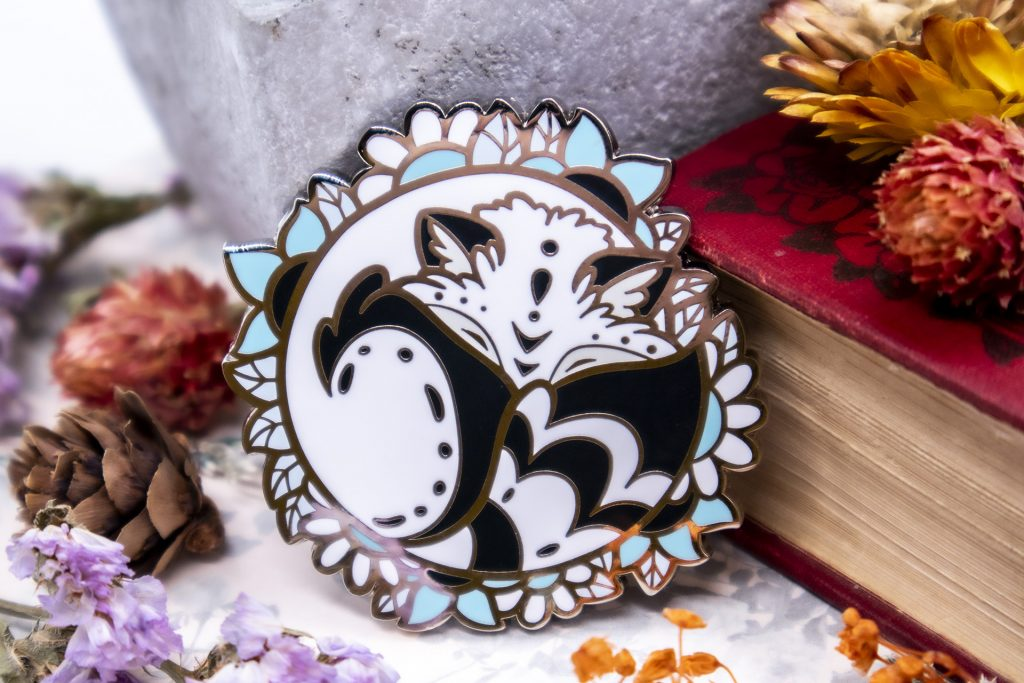 A hard enamel pin showing a sleeping white fox, curled up among a border of flowers and leaves.