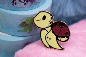 Cartoon-style Hawksbill Sea Turtle enamel pin with rose gold plating.