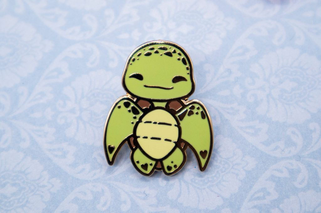 A cartoon-style Green Sea Turtle enamel pin with gold plating.