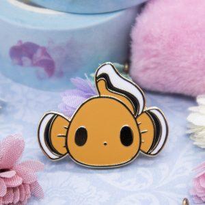 A wide-eyed, cartoon-style clownfish enamel pin.