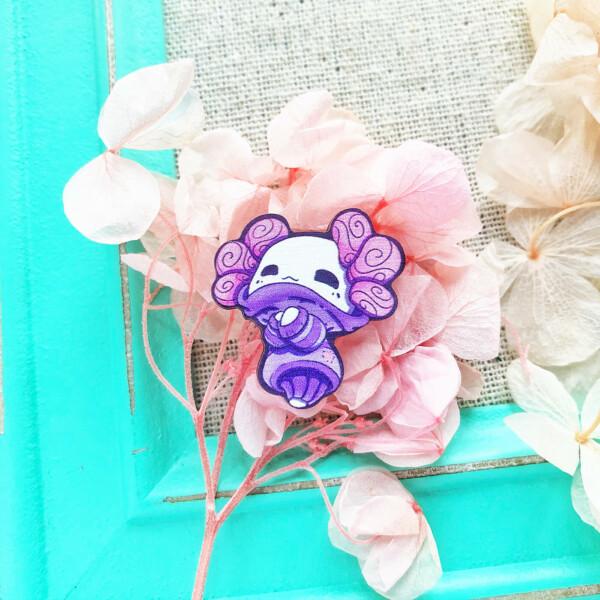 A kawaii pin badge of a cute axolotl dressed up in a cozy sweater. Illustrated by Evy Benita.