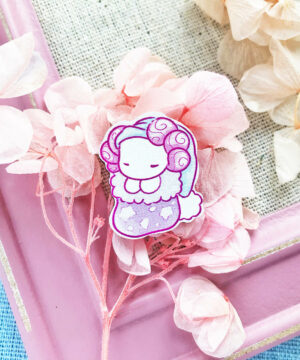 A cute pin badge showing an axolotl sleeping in a Christmas stocking. Designed by Evy Benita.