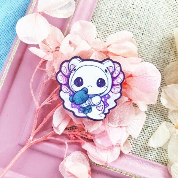 """An adorable axolotl wooden pin featuring Evy Benita's """"Lottie the Lotl"""" dressed up as a polar bear."""