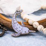 Elegant narwale enamel pin with iridescent glitter. Designed by Evy Benita.