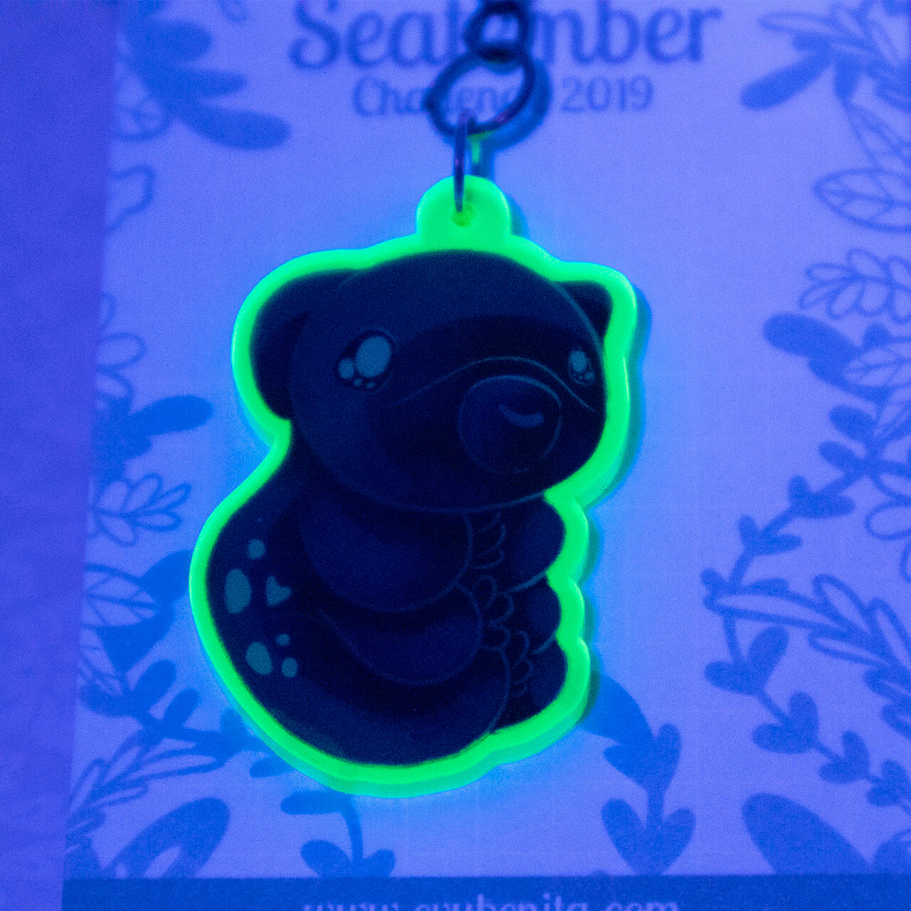 "Shows an acrylic charm featuring a cartoon style tardigrade, or ""water bear"". The charm is made from a material that lights up under UV lamps. The photo demonstrates the vibrant glow."