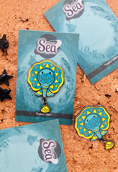 A vibrant and cartoon-style stingray enamel pin with dangle tail