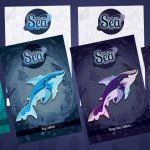 Showing a visual mockup of the four backing card designs for my Cosmic Sea enamel pin collection. A visual of an enamel pin shark is placed on top of each card to demonstrate how the full products will look when finished in production.