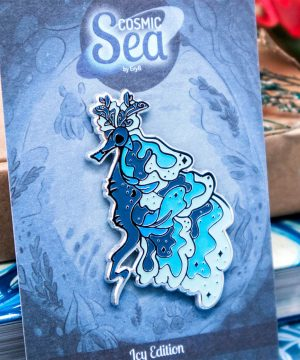 "A blue glow in the dark weedy seadragon enamel pin by Evy Benita, presented on a backing card which reads ""Cosmic Sea - Icy Edition""."
