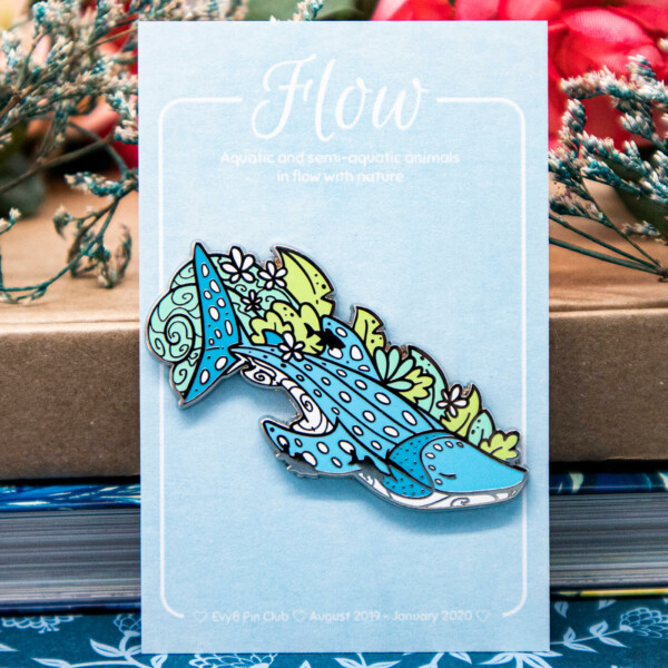 "A hard enamel pin featuring an illustrated whale shark surrounded by seaweed and the silhouettes of smaller sucker fish. The whale shark has a tranquil pose and facial expression. The enamel pin is mounted on an eco-friendly, light blue backing card that reads ""Flow: Aquatic and semi-aquatic animals in flow with nature"". The card is placed in front of books stocked on top of one another, and a selection of dried flowers."
