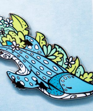 A hard enamel pin featuring an illustrated whale shark surrounded by seaweed and the silhouettes of smaller sucker fish. The whale shark has a tranquil pose and facial expression.