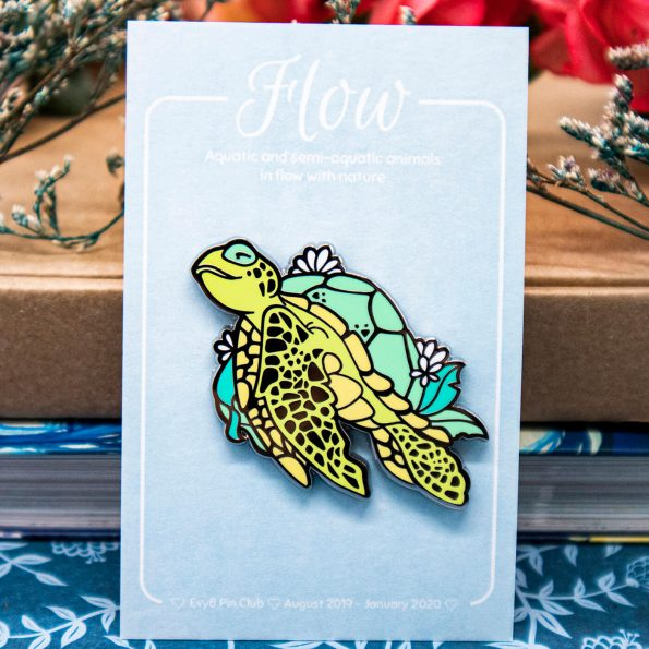 An enamel pin featuring an illustrated green sea turle with a happy and peaceful expression, floating diagonally upwards in a calm pose.