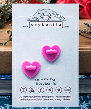 The back of an enamel pin backing card, featuring pink heart shaped rubber pin clutches.