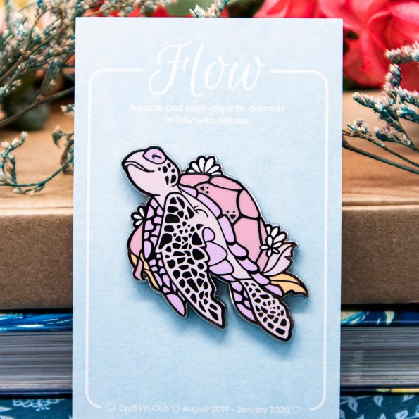 An enamel pin featuring an illustrated pink sea turle with a happy and peaceful expression, floating diagonally upwards in a calm pose.