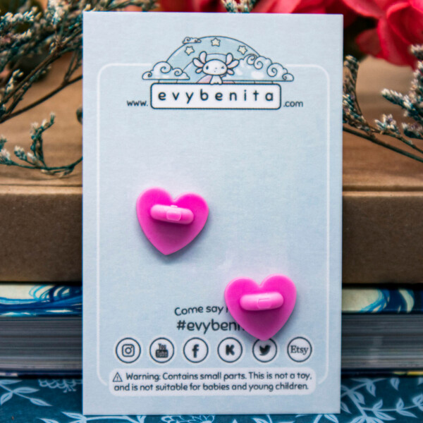 The back of an enamel pin backing card, showing two pink rubber clutches shaped like hearts.