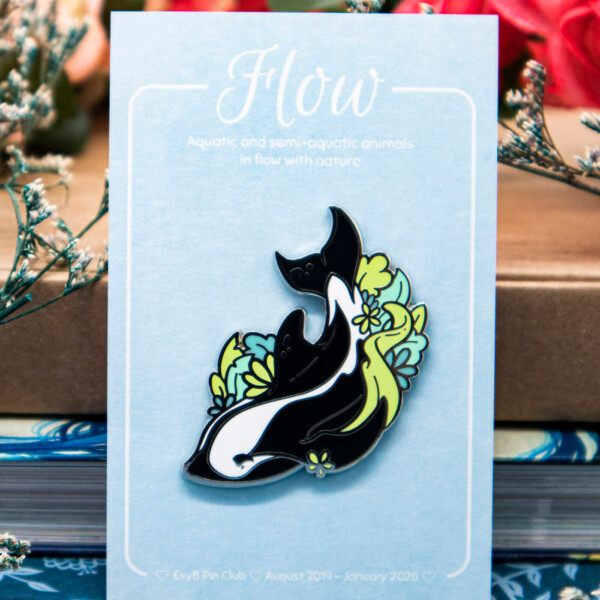 A hard enamel pin with raised, silver-plated outlines, featuring the rare hourglass dolphin decorated by green foliage