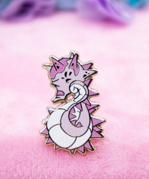 """A cute kawaii-style lapel pin featuring a spikey """"hedgehog"""" seahorse. The pin is created with pink shades of hard enamel, giving the enamel a smooth surface. The design is elevated with raised metal edges in gold plating."""