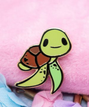 A cute, cartoon-style lapel pin featuring a baby sea turtle with big eyes smiling right at you. The design is framed by raised metal in gold-style plating.