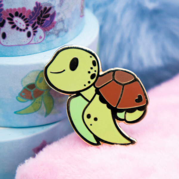 Cute cartoon-style hard enamel pin featuring a green baby sea turtle. The sea turtle is smiling and looking excitedly outward, as if on an adventure.