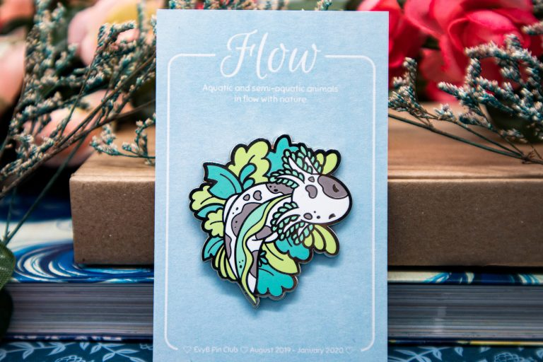 Cute speckled axolotl lapel pin on a recycled backing card.