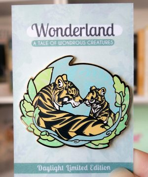 An enamel pin in a semi-realistic style featuring two tigers (parent and cub) facing each other in a sweet and peaceful setting.
