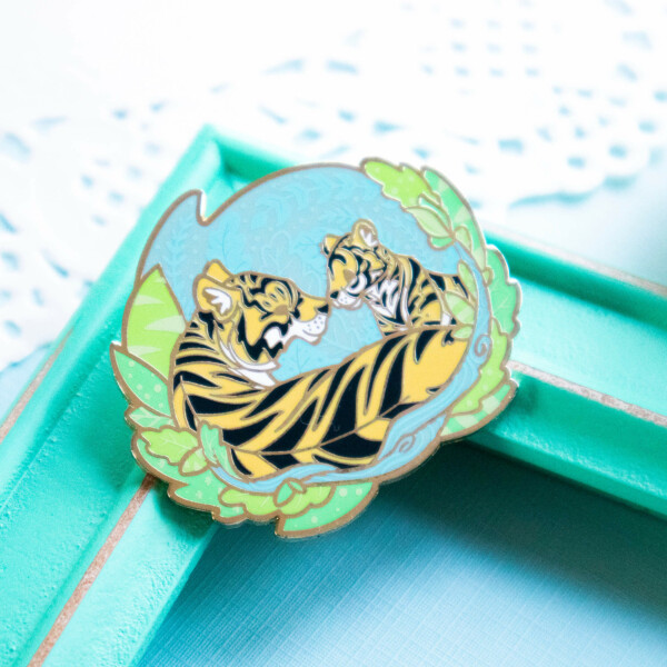 A beautiful tiger enamel pin depicting a Bengal Tiger mother with her new cub. The tiger family is depicted in a semi-realistic art style, and lay surrounded by screenprinted foliage. This pin badge is made from fresh green, blue and grey shades of hard enamel, and feature raised outlines in gold plated metal.