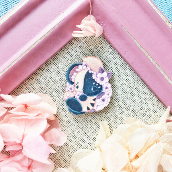 A wooden pin featuring a Japanese bunny covered in sakura flowers. The bunny is illustrated in a lovely chibi kawaii aesthetic.