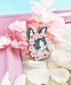 A wooden pin badge featuring a printed-on design of a hop bunny. The bunny is decorated by small cherry blossom drawings, and displayed within a pink frame. This pin has a very pastel pink aesthetic.