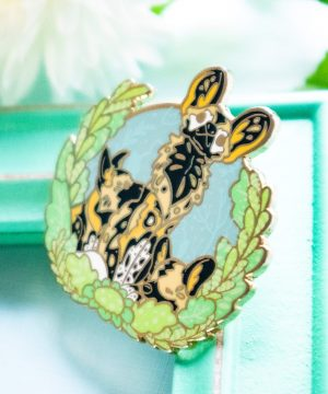 A beautiful enamel pin depicting an African Painted Dog mother with her two pups. The wild dog family is depicted in a semi-realistic art style, and sit surrounded by screenprinted foliage. This pin badge is made from fresh green, blue and grey shades of hard enamel, and feature raised outlines in gold plated metal.